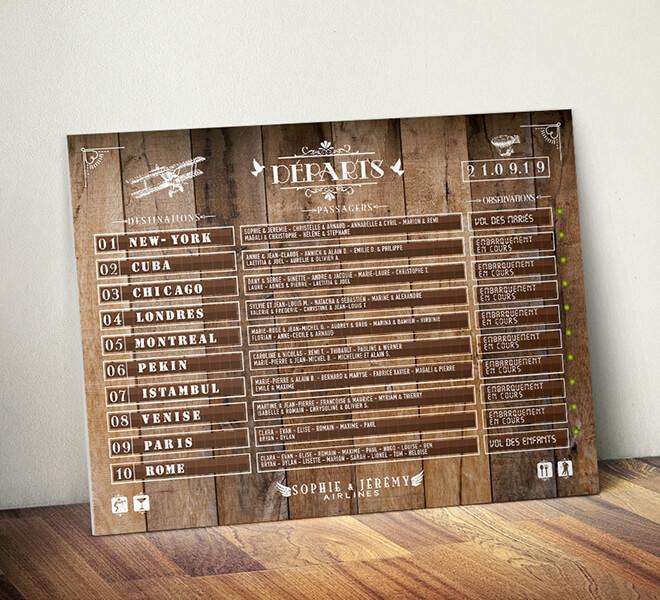 Plan de table de mariage original sous forme de panneau d'aéroport, board d'embarquement avion pour un mariage sur le thème du voyage - fond effet bois - avec les destinations pour chaque table © www.alpagart.fr